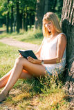 Portrait of young woman reading a book. Outdoor portrait of young woman sitting in the park under a tree and reading a book Stock Photography