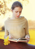 Portrait young woman reading book in sunny autumn Royalty Free Stock Photography