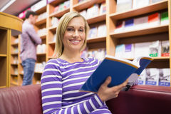 Portrait of young woman reading book. Portrait of young women reading book in library Royalty Free Stock Photography
