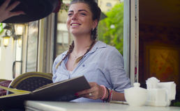 Portrait of young woman reading menu in the cafe Royalty Free Stock Photography