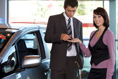 Portrait of young woman receiving car key from car salesman Royalty Free Stock Photos