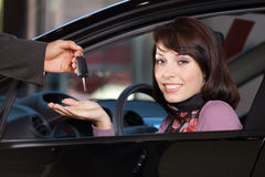 Portrait of young woman receiving the car keys from car salesman Stock Image