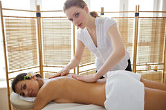 Portrait of young woman receiving massage from masseuse Royalty Free Stock Photography