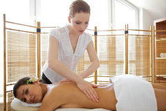 Portrait of young woman receiving massage from masseuse. Portrait of young women receiving massage from masseuse Stock Photo