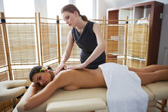 Portrait of young woman receiving massage from masseuse Royalty Free Stock Photo