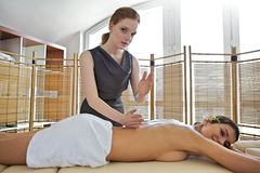 Portrait of young woman receiving massage from masseuse. Portrait of young women receiving massage from masseuse Royalty Free Stock Image