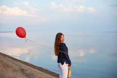 Portrait of young woman with red air balloon and present bag near the calm sea or lake shore. Clouds are reflected on royalty free stock photos