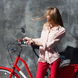 Portrait young woman in red chino holding hands on her red vintage bicycle, standing against gray wall. The wind blows her hair. O Stock Photography