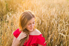Portrait of a young woman in red dress on a background of golden oats field, summer outdoors. Royalty Free Stock Photo