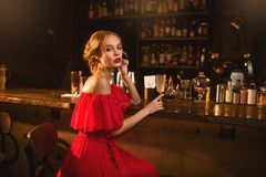 Portrait of woman in red dress at the bar counter Stock Photo