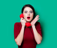 Portrait of young woman with red handset Royalty Free Stock Image