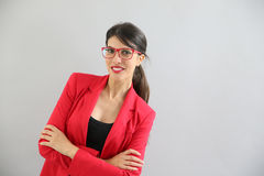 Portrait of young woman in red jacket and red eyeglasses. Beautiful brunette girl with red jacket and eyeglasses, isolated Stock Photography