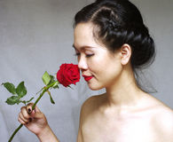 Portrait of young woman with a red rose. Young woman with a red rose in the studio Royalty Free Stock Images