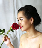 Portrait of young woman with a red rose. Young woman with a red rose in the studio Royalty Free Stock Image
