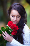 Portrait of young woman with red roses Royalty Free Stock Image