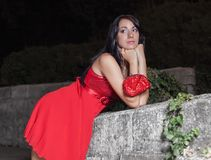 Portrait of young woman in red sleeveless dress. Attractive long haired brunette in red sundress posing with his head in his hands in night park Royalty Free Stock Images