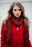 Portrait of young woman in red winter coat and scarf. Outdoors Stock Images