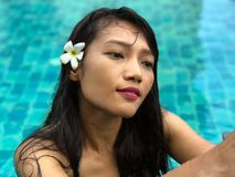 The portrait of young woman relaxes in blue pool. royalty free stock images