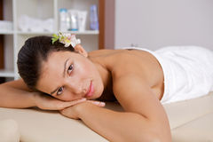 Portrait of young woman relaxing on massage table Stock Photography