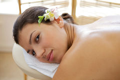 Portrait of young woman relaxing on massage table Stock Image