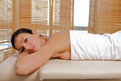 Portrait of young woman relaxing on massage table Stock Photo