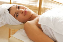 Portrait of young woman relaxing on massage table Stock Images