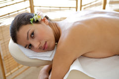 Portrait of young woman relaxing on massage table Stock Photos