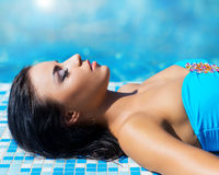 Portrait of a young woman relaxing in a pool Stock Photo