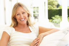 Portrait Of Young Woman Relaxing On Sofa Royalty Free Stock Photography