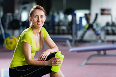 Portrait of young woman resting after workout at gym. stock photos