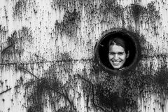 Portrait of a young woman in a round window in a rusty iron wall. Black-and-white photo Royalty Free Stock Photo