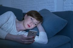Portrait of young woman 30s lying on bed couch late at night at home using social media app on mobile phone tired and sleepy. In internet addiction concept Stock Photography