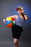 Portrait of a young woman in sailor costume. Portrait of an attractive young woman in sailor costume holding a beach ball  over gray background Stock Photos