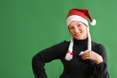 Portrait of young woman with santa claus hat standing on green background Stock Photos
