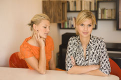 Portrait of 2 young woman sat at a table Royalty Free Stock Photo