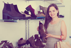 Portrait of young woman selecting loafers. In footgear center Stock Photos