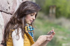 Portrait of young  woman sending sms ,outdoor Stock Photography