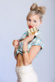 Portrait of young woman girl eating chocolate on blue Stock Images