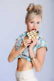 Portrait of young woman sexy girl eating chocolate on blue Royalty Free Stock Image