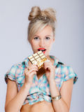 Portrait of young woman sexy girl eating chocolate on blue Stock Images