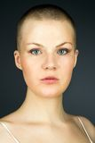 Portrait of young woman with shaved hairstyle. Against dark background Royalty Free Stock Image