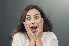 Portrait of young woman with shocked facial expression Stock Photo