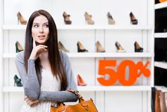 Portrait of young woman in shop with 50% sale royalty free stock images