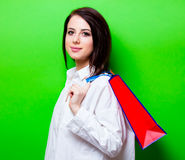 Portrait of young woman with shopping bag. Portrait of the beautiful young woman  with red shopping bag on the green background Stock Image