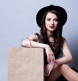 Portrait of young woman with shopping bag. Portrait of the beautiful young woman with shopping bag sitting on the grey background Royalty Free Stock Photography