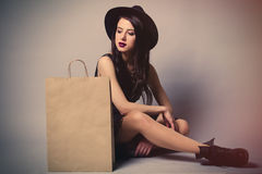 Portrait of young woman with shopping bag. Portrait of the beautiful young woman with shopping bag sitting on the grey background Stock Image