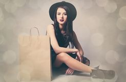 Portrait of young woman with shopping bag. Portrait of the beautiful young woman with shopping bag sitting on the grey background Stock Images