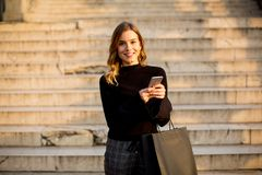 Young woman with shopping bag and mobile phone outdoor. Portrait of young woman with shopping bag and mobile phone outdoor Royalty Free Stock Photography