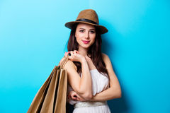 Portrait of the young woman with shopping bags. Portrait of the beautiful young woman with shopping bags on the blue background Stock Photography