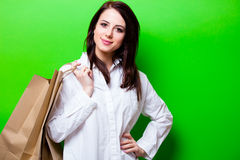Portrait of young woman with shopping bags. Portrait of the beautiful young woman with shopping bags on the green background Royalty Free Stock Images